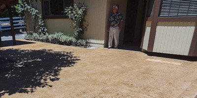 A man stands looking at his concrete patio that has no cracks anywhere throughout.