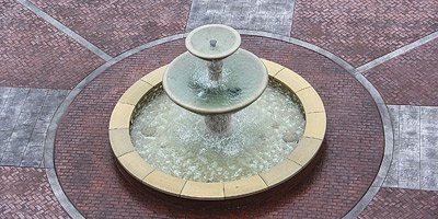 Three tiered water fountain on a stamped concrete pad.