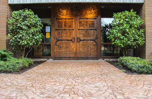 Large wooden double doors with stamped concrete leading up to it.