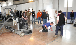 Polishing machine sits on the concrete slab while attendees look on.