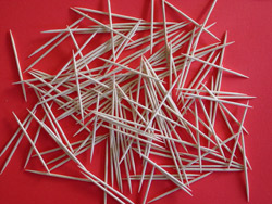 Toothpicks piled on top of a red backdrop.