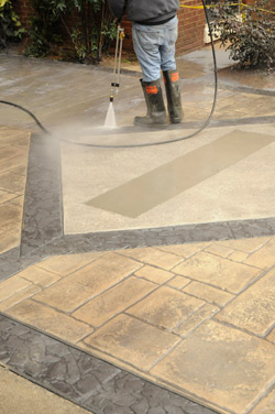 Pressure washing the concrete to prepare for final sealing coat.