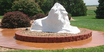 Large white lion sculpture sits upon a concrete circle.