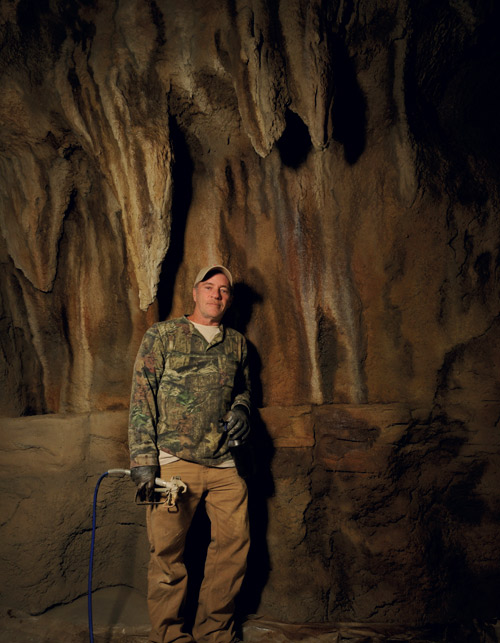 Thom Hunt stands next to one of his concrete stalagmite walls.