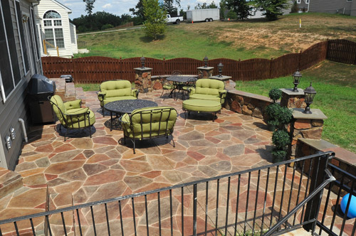 Circular stamped concrete backyard patio enhances the lime green cushioned iron patio furniture.