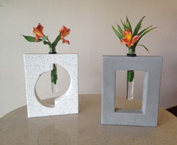 Concrete flower vase holders. Holds glass cylinders.