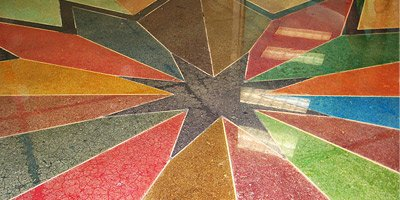 Stained concrete floor in a color burst of rays coming out of a star.