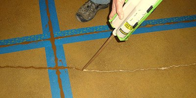 Prior to polishing a concrete floor, cracks are being filled with a two part epoxy