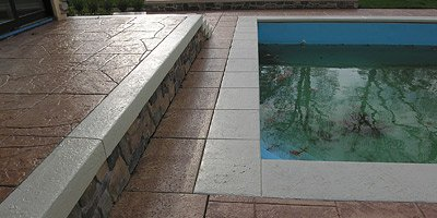 The combination of pools and stamped concrete doesn't necessarily spell disaster. For one thing, when a stamped concrete surface near a pool is slick, a topical sealer, not the texture, is often the culprit.