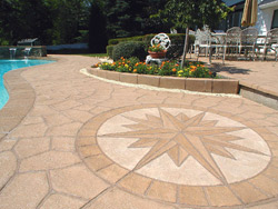 This resurfaced pool deck and patio in Lake Hiawatha, N.J., features Unique Concrete NJ's custom-made field stone stamp and medallion. The integrally colored concrete was stained with a homemade water-based system and sealed with Kingdom Products' Kingdom Cure, a high-solids solvent-based sealer.  Photo courtesy of Unique Concrete NJ