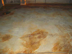 A hard-troweled floor after the acid stain was cleaned off. The blotchy finish is the result of a lack of penetration and reaction on the part of the stain.