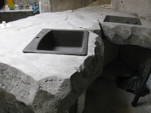 two sinks have been placed into a concrete countertop of sorts that is carved and custom