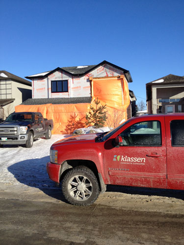 A red truck sits in front of a house that is being prepped for cold weather carving.