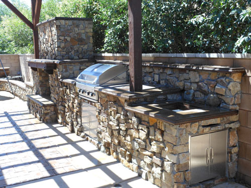 A look at an outdoor kitchen with stone facade and concrete countertops.