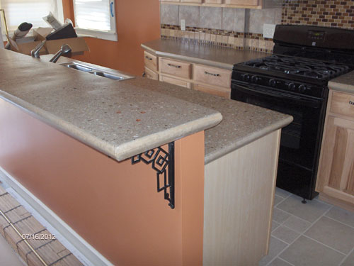 A double tier countertop in a kitchen in light gray with aggregate.