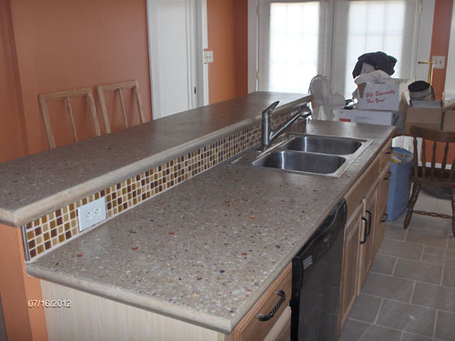 A concrete countertop in a kitchen with a bar top on the back.