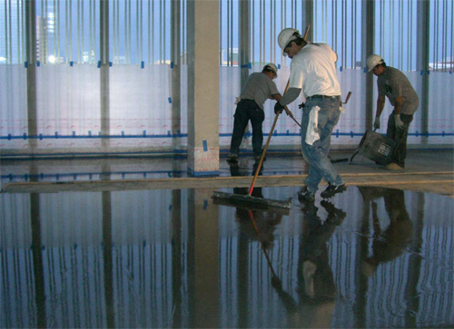 Workers using brooms and finishing aids to install self-leveling toppings.