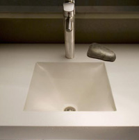 Sleek concrete sink with metal faucet.