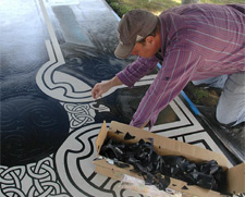 A contractor removes the adhesive vinyl of the stencil in areas that will be colored with stain.