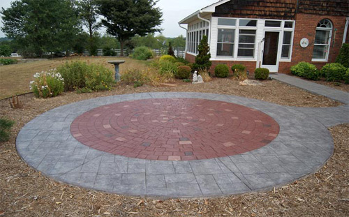 A radial stamped patio that is gray and red and looks like pavers.