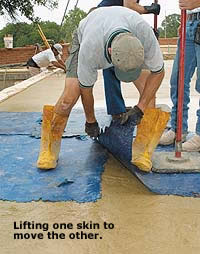 Lifting Concrete Skins while moving another skin next to it. Man in yellow boots leaning over manipulating concrete skins.