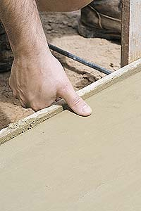Contractor testing the cure of a concrete slab before using texture skins.