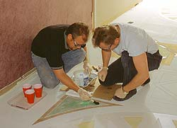 Two men staining within a concrete stencil. Water based concrete stains are a versatile tool to use on concrete floors.