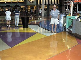 Mesmerizing water based stained concrete floor with geometric styling in a shopping center food court.