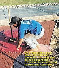 Woman using concrete stamps and concrete skins on a integrally colored concrete driveway approach.