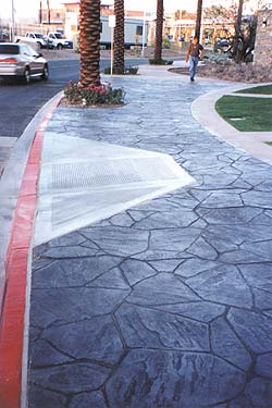 Increte Systems flagstone shaped stamp used on this city sidewalk with contrasting colors in dark grey and black.