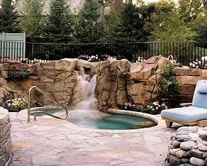 synthetic rocks from concrete surrounding a hot tub with a water fall tumbling down the faux rocks into the hot tub.