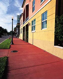 Brushed Concrete Sidewalk in deep red contrasts with a yellow stucco building.