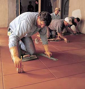 Four men working on an integrally colored floor cleaning up the decorative joints. Once used almost exclusively as an exterior building material, Davis Colors are now equally at home in residences and commercial interiors.