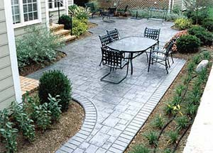 Stamped concrete backyard patio in dark chocolate brown spans well with black patio furniture.