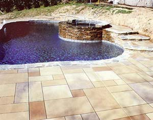 Stamped concrete has individual tiles stained in earth tones with a round hot tub set to the side.