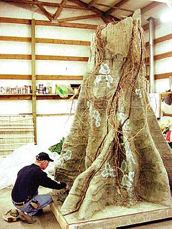 Concrete tree trunk being modified by a Lakeland employee.