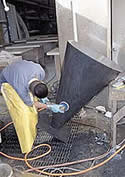 Buddy Rhodes Studio finishing a large concrete cylinder in dark gray.