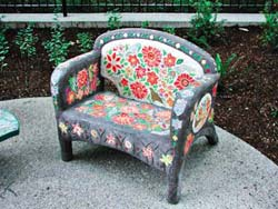 A concrete chair outdoors that has been colored and decorated with a floral design.