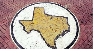 A stencil was used on a concrete surface in the shape of Texas by Stencil Systems