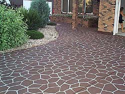 Stenciled concrete brick red driveway with white colored grout by Stencil Systems