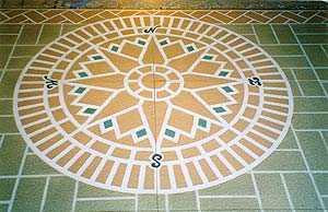 A stencil was used to create this colorful compass surrounded by a stenciled brick patterned floor by Stencil Systems