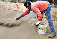 Throwing color hardener onto a fresh concrete slab prior to stamping or texturing the concrete.