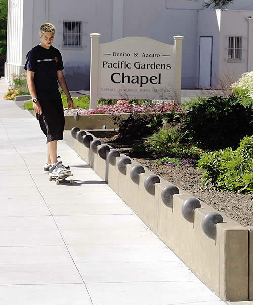 Skateboarder skates by a decorative feature built into the concrete to prevent damange