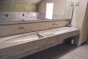 Simple gray concrete countertops by Fu-Tung Cheng give this bathroom an industrial and sleek look.