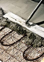 Close up view of placing concrete over radiant heat coils.