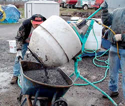 Pouring concrete mix into a wheel barrow after mixing the pigment into wet concrete in a small portable mixer.