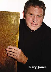 Colormaker Floors - Gary Jones holds a sample board of their concrete coatings product.
