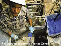 Yonas Zeru of Colormaker Floors holds up blue pigment in a measuring cup to be added to a concrete admixture.