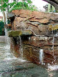 Faux Rock Pond shows discoloration from the constant contact with water has white efflorescence appearing.