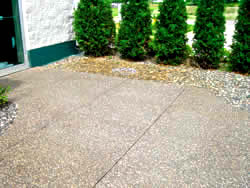 Exposed aggregate patio stained by iron rich sprinkler water has been cleaned using a specialized solution and looks new.